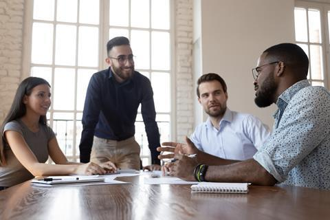 A group of four colleagues chat around a table  - 97395 istock1176842746 974702 crop - 'Safe space': judge highlights benefit of office returns | News